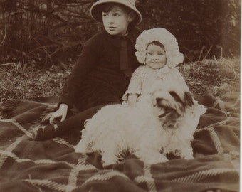 Brother sister, outdoor photo, Social history, check picnic blanket, white dog, vintage hats, antique snapshot, vernacular  (rppc/ch237)