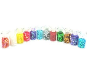 12 mini glass jars containing Rhinestones, glitter...
