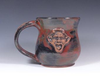 Satyr mug.  Handmade stoneware pottery.  Burgandy and black art glaze.