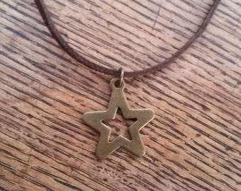 Antique brass tone cut out star pendant necklace - on brown flat suede leather cord