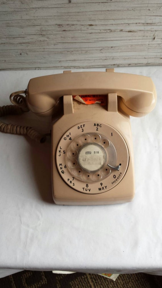 Vintage 1977 Bell System Rotary Phone in Beige. In Working Condition. Nicely embossed Bell System in 2 Places. Made by Western Electric.