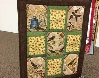 log-cabin quilted wall-hanging of seasons with birds