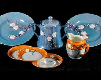 Nippon Lustreware in blue and in orange with cherry blossom motif includes sugar and creamer with 3 saucers and 2 salad plates