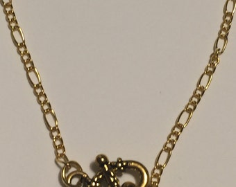Gold tone figaro chain with toggle clasp