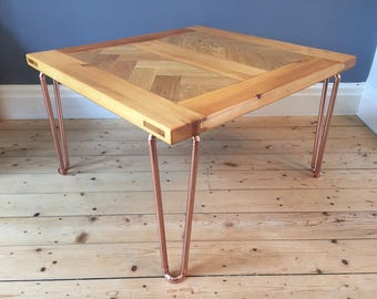 Coffee table in a retro industrial style with copper pipe hairpin legs and reclaimed door with oak herringbone inlay  top