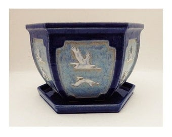 A handmade stoneware planter / plant pot with high relief decoration of flying storks