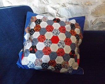 Hand sewn patchwork cushion cover with blue and red hexagons