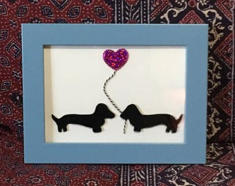 Vinyl Dachshunds holding heart balloon in frame