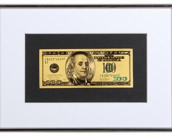 Gilded 100 dollars banknote  in frame