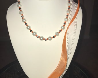 The Shawna.   Glass pearl necklace with Orange and White ribbons for the ties.