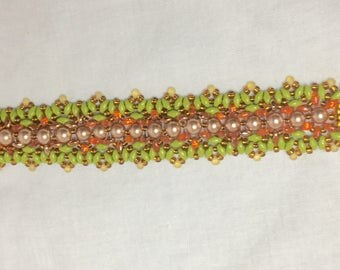 A beautiful bracelet woven from lime green and red/gold superduos, woven either side of cream Swarovski pearls. The clasp is gold filigree.