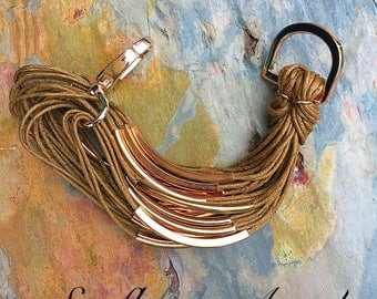 Multi stranded tobacco twine bracelet, with gold bars and large lobster clasp.