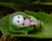 Little Elven baby wrapped in green clotch with flower glass bead