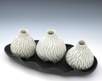 Three white carved porcelain vases with black tray