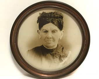 Antique photograph sepia toned portrait of old woman, framed in round brass frame, c1900, creepy