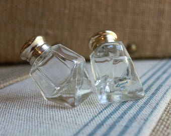 A pair of vintage salt & Pepper shakers clear glass and off centered