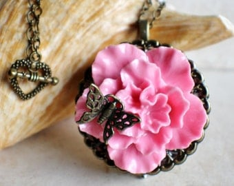 Music box locket, round locket with music box inside, in bronze with pink carnation, filigree butterfly and bronze accents