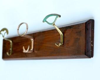 Coat rack with three brass hooks