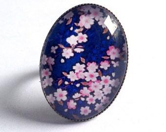 Bague ovale cabochon fleurs de cerisier sur fond bleu, en bronze, romantique.