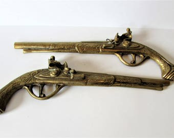 This is Pair Of Cast Brass Flintlock Dueling Pistols -  Wall Mount Display Pieces.