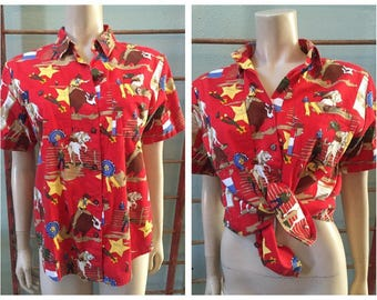 Cute Rodeo Woman's short sleeve red top by Sharon Young with bull riders, cowboys, horses, and wranglers / size 6
