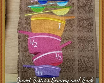 Stacked dishes measuring cups and spoons kitchen towel