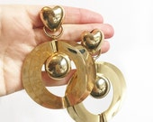 Super large gold tone costume statement clip on earrings with hearts and hoops.