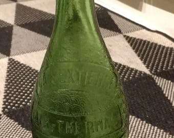 """Old bottle in blown glass green, comes from the baths of Aix en Provence, to the of the France. """"The Sextienne, thermal Aix"""