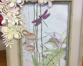 A water coloured tinted picture with decorated frame