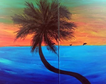Palm tree and dolphins at sunset.