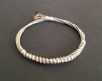 A handmade 4 string recycled guitar string bracelet/bangle silver