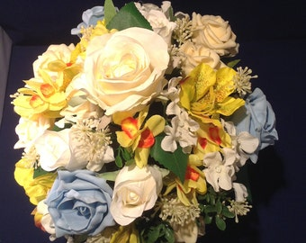 Brides  bouquet in spring flowers and  roses with cream and pale blue roses, narcissi,  alstromeria. Finished with satin ribbons.