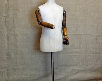 Vintage mannequin, child, calico with adjustable articulated wooden arms, on cast iron base