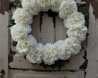 Lovely, simple grapevine wreath with white/light ivory carnations and greenery