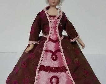 Porcelain lady with dress made in burgundy wild silk, scale 1:12. Dollshouse miniature.