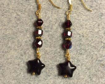 Dark ruby red Czech glass star bead dangle earrings adorned with dark red Czech glass beads.