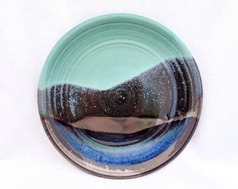 Glazed pottery plate with green, blue, and black glaze in a mountain landscape pattern
