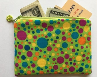 Green polka dot coin purse with yellow flower charm