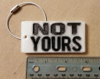 """A snarky, """"NOT YOURS"""" luggage tag"""