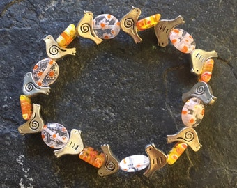 Sweet silver colored birds with orange and yellow glass beads stretchy bracelet