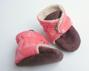 Coral baby booties with white triangle design. 6-9 months.