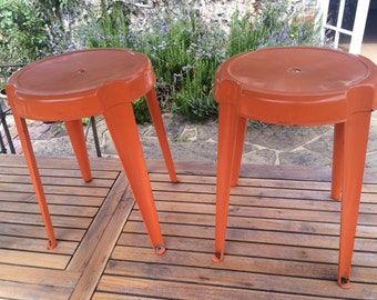 A matching pair of orange Tolix style low stools