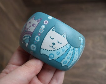 Wooden bracelet with a painted sleepy and cute cats . White, purple, turquoise.