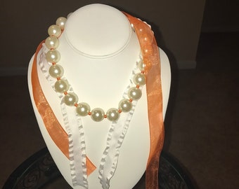 The Shawna 2.0.   Glass pearl necklace with Orange and White ribbons for the ties.