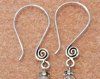 Swirled dangle earrings with diamond and seed beads.