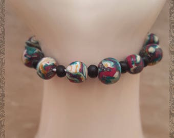 Multi-coloured Beaded Bracelet, which has black smaller beads between larger ones. On an elasticated band. 20cm approximate size.