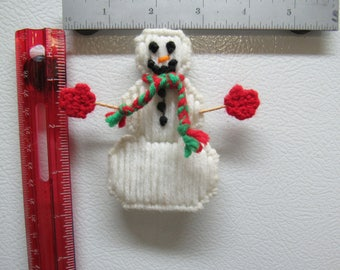 Winter snowman has red and green scarf and red gloves is made of plastic canvas and yarn with a magnet glued to back