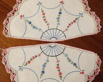 A trio of fan-shaped doilies, beautiful in pinks and blues