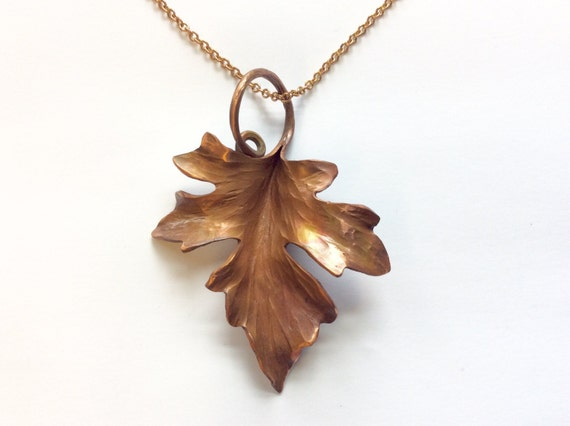 An artfully smithed copper maple leaf pendant on a 20 inch brass chain