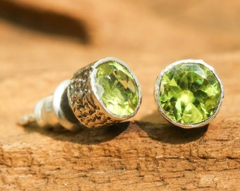 Round faceted peridot earrings faceted in silver bezel setting with post style and backing